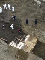 Workers wearing protective gear bury bodies in a trench on Hart Island in New York City on April 9.