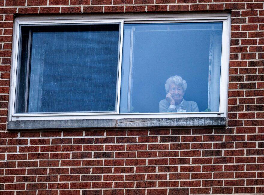 "A resident of the Goodwin House senior living community, looks on as she listens to the DC area motown band ""The Tribe"" play a social distance concert in their parking lot in Arlington, Virginia, during the coronavirus pandemic on April 14, 2020. (ANDREW CABALLERO-REYNOLDS/AFP via Getty Images)"