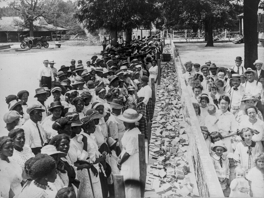 Crowds of African-American and white people are separated by a long counter covered with slices of bread at F.M. Gay's annual barbecue, held on his plantation every year in Alabama.