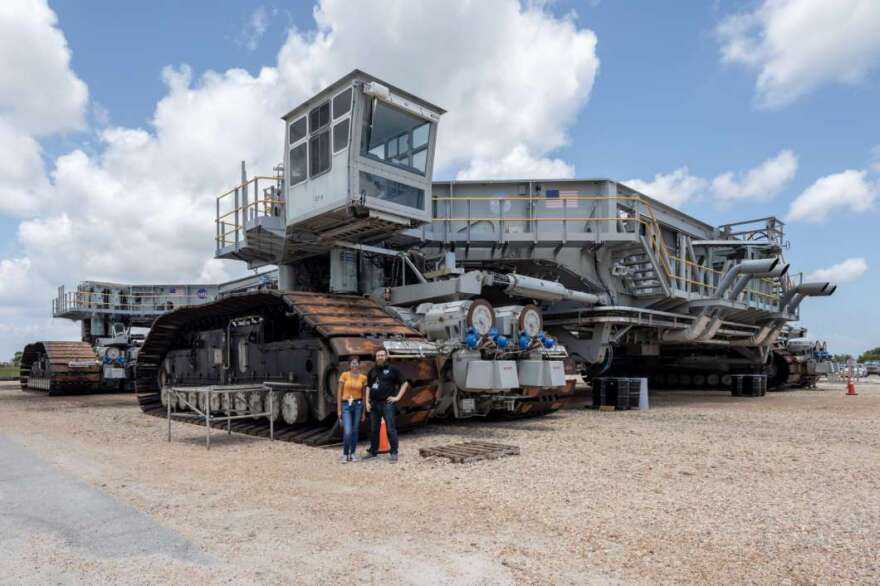 NASA's Crawler-Transporter will give SLS a piggy-back ride to the launchpad. Florida Today's Anotnia Jaramillo & WMFE's Brendan Byrne stand in front of the Crawler's tred for scale.