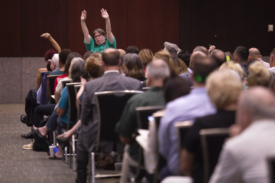 A forum attendee waves both hands in the air, hoping to ask a question about Austin's public camping ordinances. The forum, one of many public discussions about homelessness in Austin in 2019, was held at the Austin Convention Center in August.