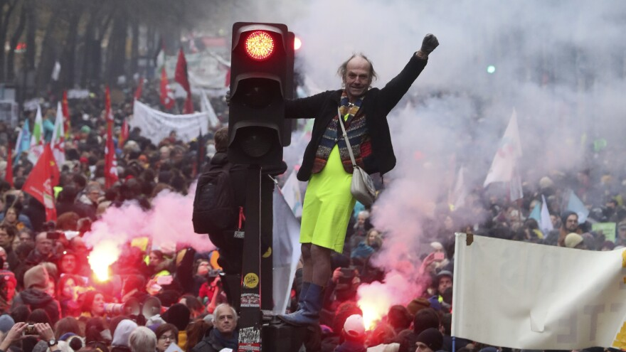 A man perched on a traffic light pumps his fist amid the chaos of a demonstration Thursday in Paris. Several thousand protesters took part in open-ended nationwide strikes, begun Thursday under union leadership.