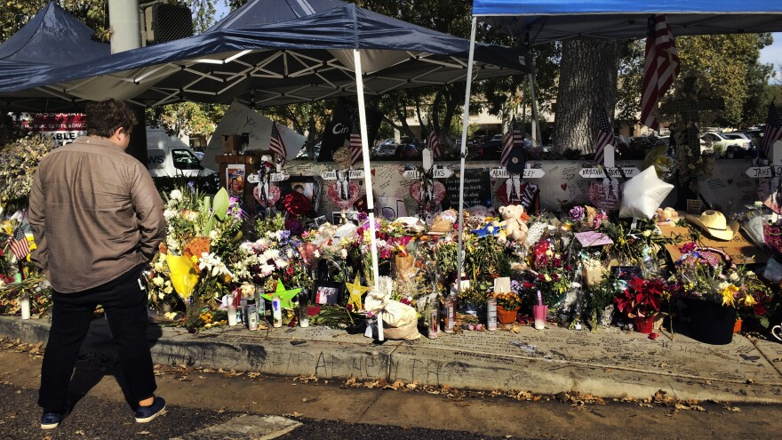 A passerby stops to look over a street side memorial to the shooting victims of the Borderline Bar in Thousand Oaks, Calif., on Tuesday. Investigators said the number of victims from the shooting at the country music bar could have been much higher based on the amount of ammunition the gunman carried.