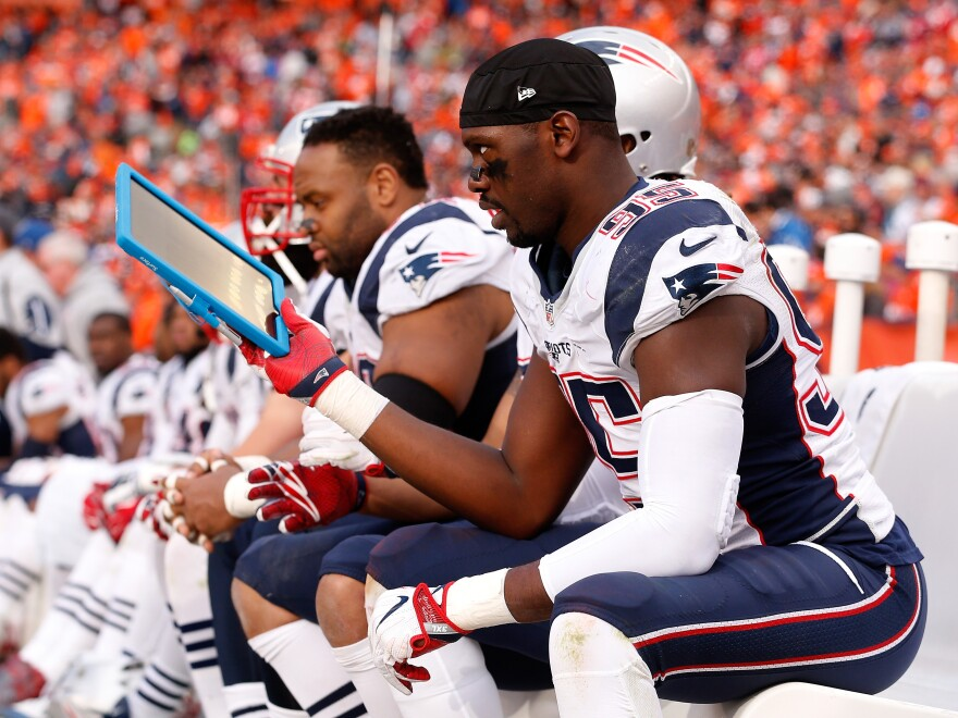 New England Patriots' defensive end Chandler Jones holds a Microsoft Surface tablet on the sideline in the third quarter of the AFC Championship game against the Denver Broncos. In the second quarter, the Patriots' tablets briefly stopped working.