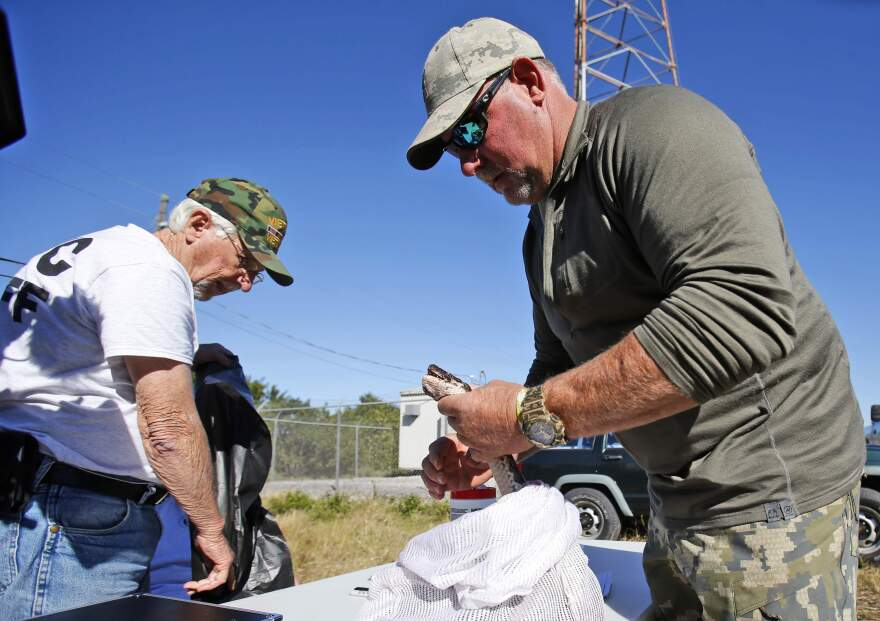 "Bill Booth, of Bradenton, turns in a dead python to Florida Fish and Wildlife Conservation Commission seasonal employee Bob Besherse, left, at a ""Python Challenge"" checkpoint Sunday in Florida Everglades."