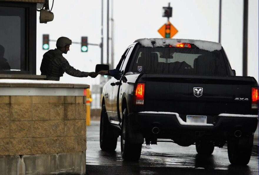 The driver of a black truck entering a secure facility hands identification to a guard