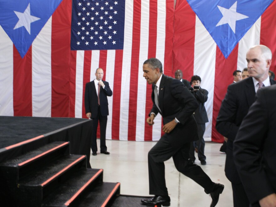 President Obama bounds to the stage in an airport hanger at Muniz Air National Guard Base, June 14, 2011, San Juan, Puerto Rico.
