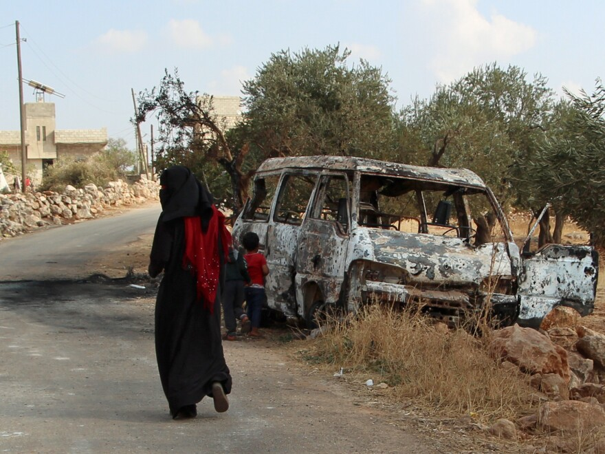 "A woman walks past a wrecked van near the northwestern Syrian village of Barisha. Local residents and medical staff told NPR that noncombatant civilians who were in the van were injured and killed last year the night of the U.S. raid on the compound of ISIS leader Abu Bakr al-Baghdadi. The military says the men were ""combatants"" but found no weapons."