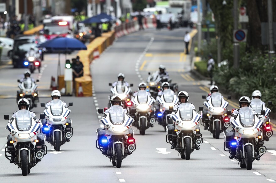 Police officers lead a motorcade for North Korean leader Kim Jong Un on the way to Singapore's Capella Hotel, the summit site.