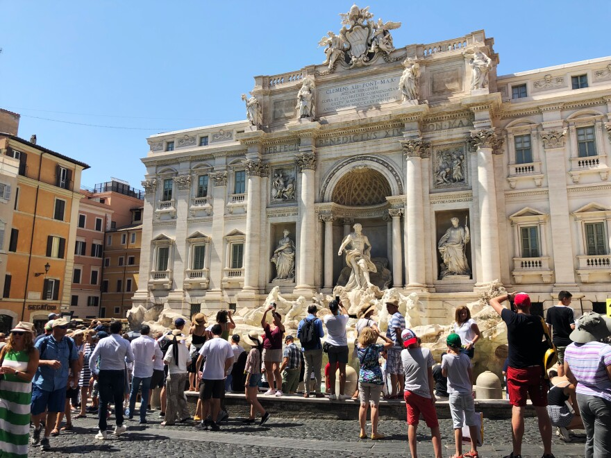 On a July afternoon, despite the 95-degree temperature, tourists visit the Trevi Fountain.