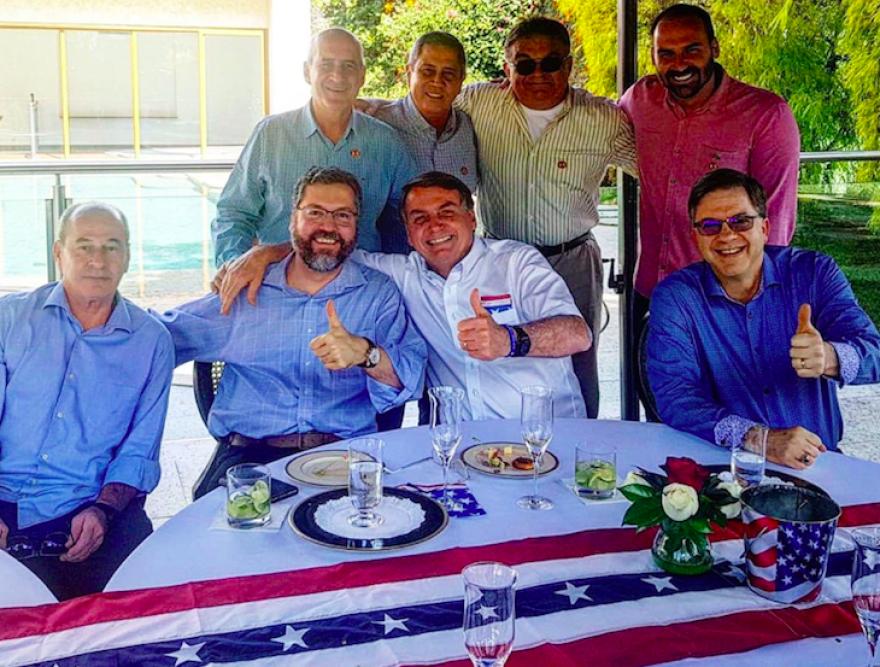 RECKLESS DISREGARD Brazilian President Jair Bolsonaro (front, white shirt) his arm around Foreign Minister Ernesto Araujo, celebrating 4th of July with diplomats at U.S. embassy in Brasilia. U.S. Ambassador Todd Chapman is seated next to Bolsonaro.
