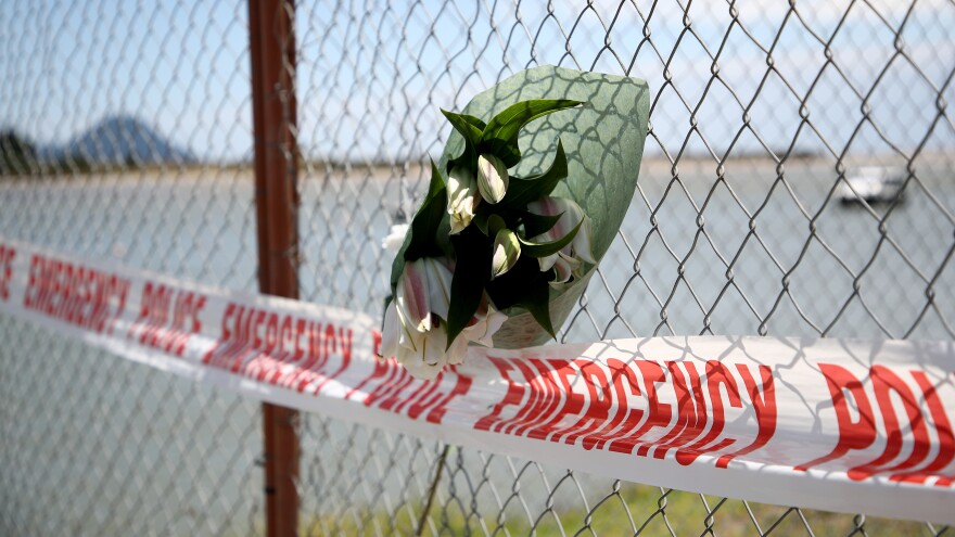 Mourners left floral tributes on a fence at the Whakatane wharf Tuesday, grieving for the victims of the eruption on White Island in New Zealand's Bay of Plenty.