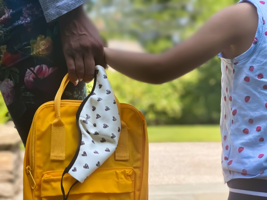 Mother and child waiting together for the school bus, holding a face mask and a backpack. (Getty Images)