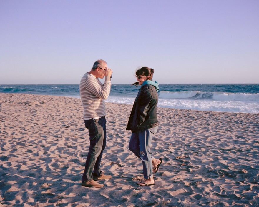 """""""You guys are all I need to heal right now,"""" Imma told the family while driving to the coast. The family sang Tracy Chapman's """"Fast Car"""" on the drive, recalls Moscovitch. Here, Imma and Moscovitch's father laugh together while bracing cold wind blows at the reopened beach on June 7."""