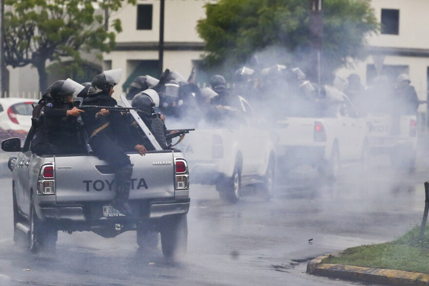 Nicaraguan police in riot gear riding on the backs of pickup trucks fire at university students on May 28, 2018.
