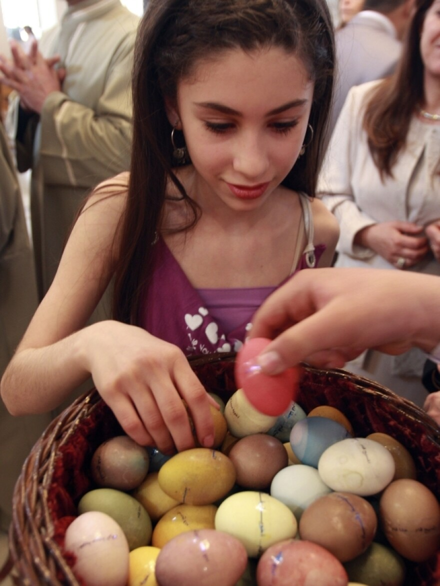 A Syrian Christian girl takes an egg from a basket at a Damascus church on Easter Sunday last year. This year's celebrations were muted, due to the country's political uprising.