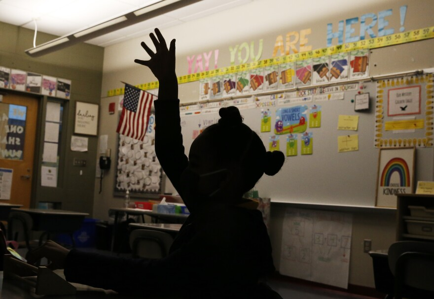 A first-grader raises her hand at Mary L. Fonseca Elementary School in Fall River, Mass., in November.