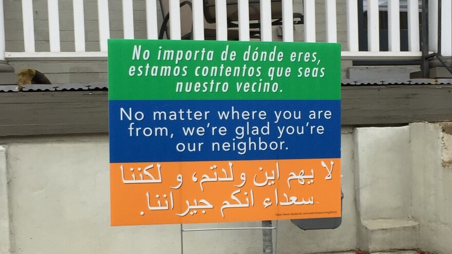 """A sign in Washington, D.C., says """"No matter where you are from, we're glad you're our neighbor,"""" in three languages. It's a message that began at a church in Harrisonburg, Va., and is spreading to communities across the country."""