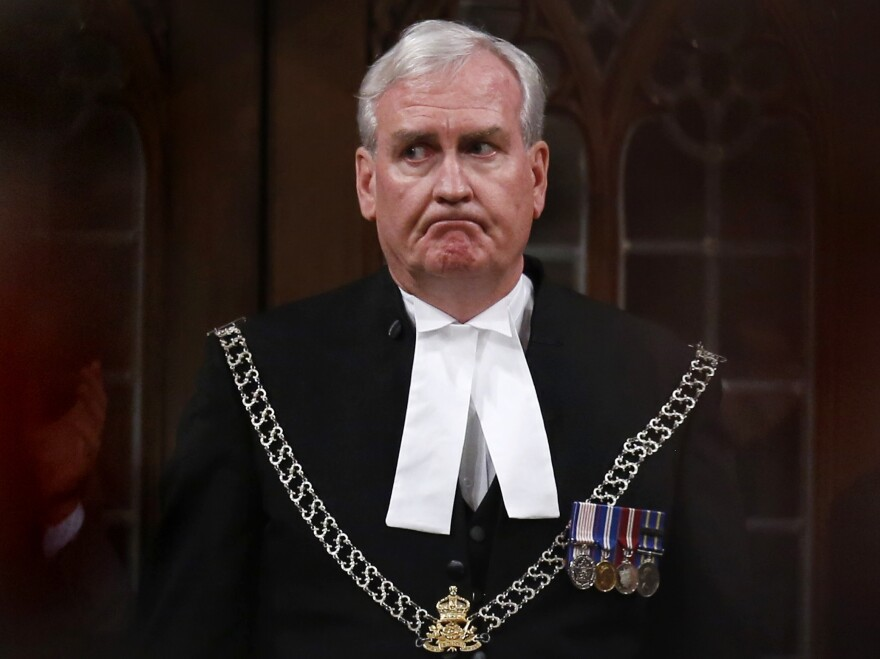 Sergeant-at-Arms Kevin Vickers is applauded in the House of Commons in Ottawa on Thursday. Vickers was credited with shooting the suspect during an attack on the Parliament complex on Wednesday.