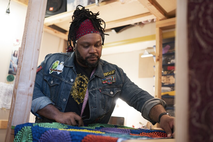 Brandin Vaughn lays out fabric to make face masks in his Cherokee Street-based boutique. Demand for the product is soaring, and it's helping him pay the bills until clothing sales pick up.