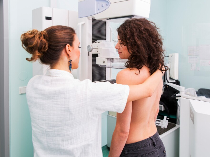 Doctor gives a young women a mammogram.