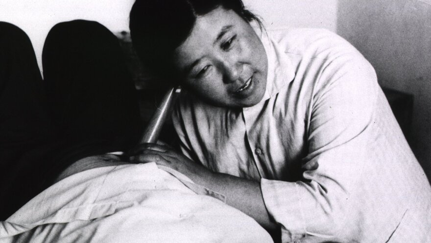 "A ""barefoot doctor"" listens to the heartbeat of a fetus. These community health workers dramatically improved maternal health in China during the 20th century."