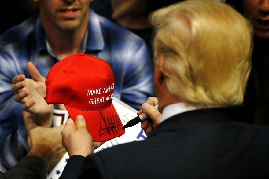 Republican presidential candidate Donald Trump signs a hat for a supporter after speaking at a campaign rally on April 11, 2016 in Albany, N.Y.
