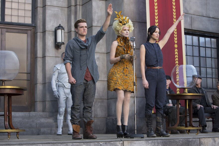 Actors Josh Hutcherson as Peeta Mellark (left), Elizabeth Banks as Effie Trinket and Jennifer Lawrence as Katniss Everdeen in a scene from the film <em>The Hunger Games: Catching Fire</em>. A fictional gesture from the Hollywood movie is being used as a real symbol of resistance in Thailand.