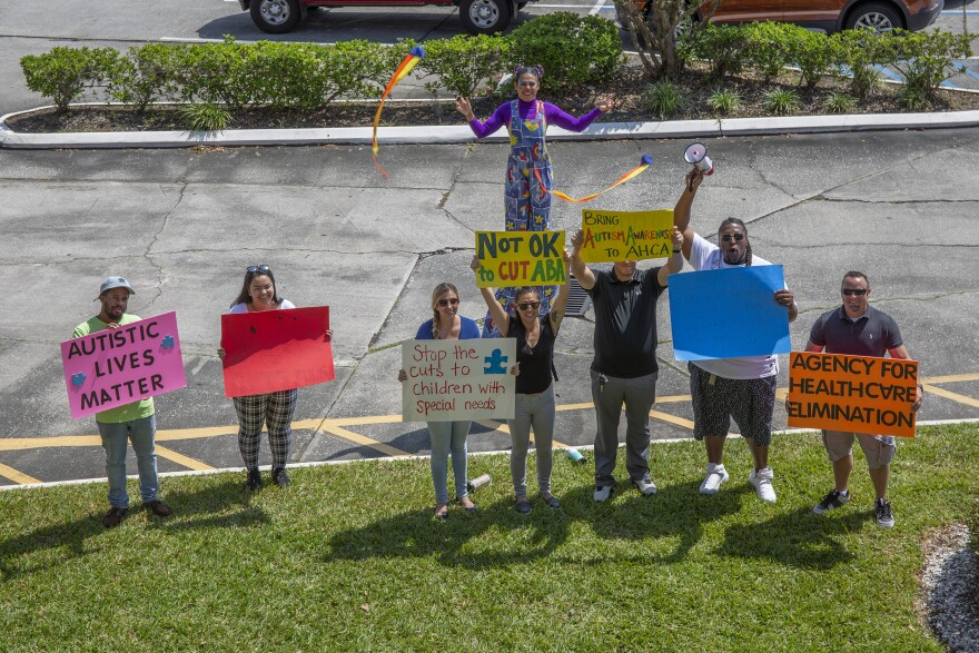 Protesters outside the Tampa AHCA office hold signs defending ABA therapy and opposing cuts to Medicaid.