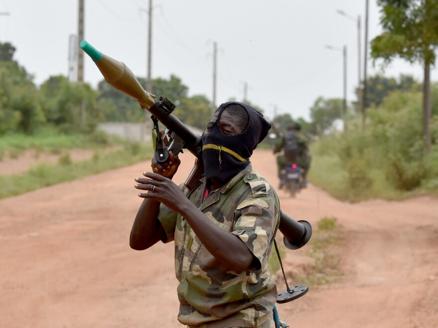 A soldier bears a rocket launcher near a military camp in the city of Bouake on Monday. Once the stronghold of the rebels that brought President Alassane Ouattara to power in 2011, Bouake is now a centerpiece of the unrest among soldiers who feel cheated of bonus pay.