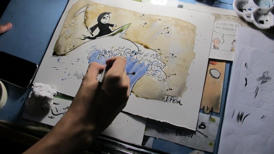 Joao Montanaro works on a cartoon illustrating the devastation the tsunami brought to Japan.