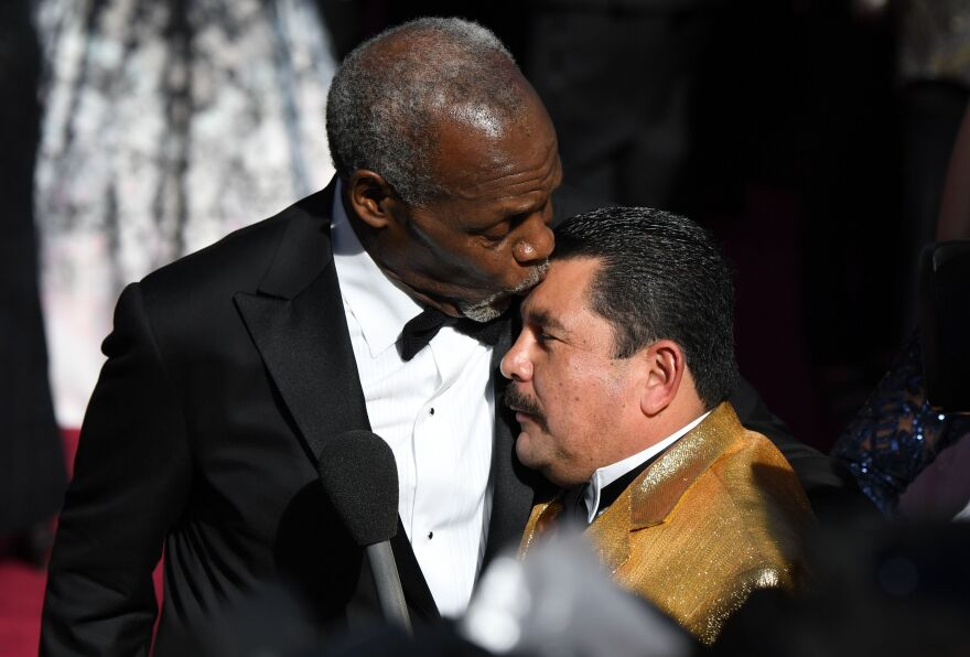 Actor Danny Glover kisses TV host Guillermo on the head.