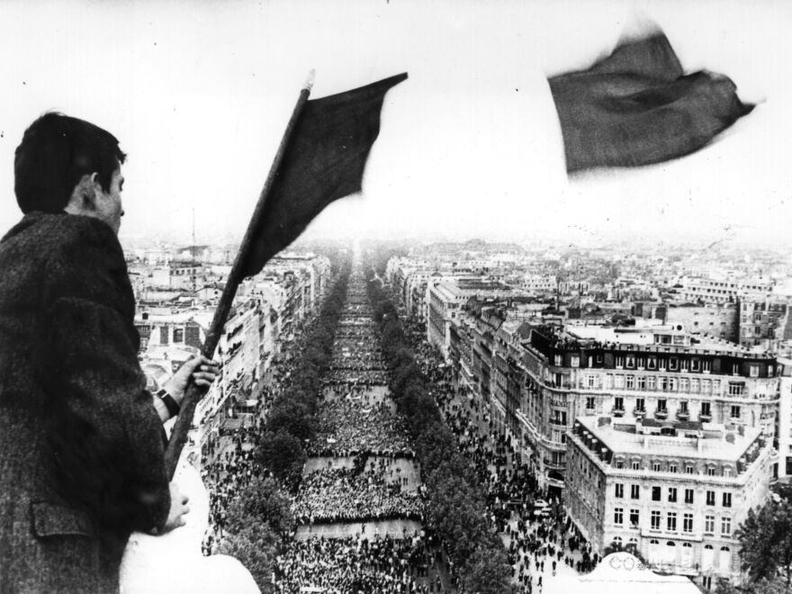 A man flies the French tricolor flag over crowds marching to the Arc de Triomphe during the Paris students' strike.