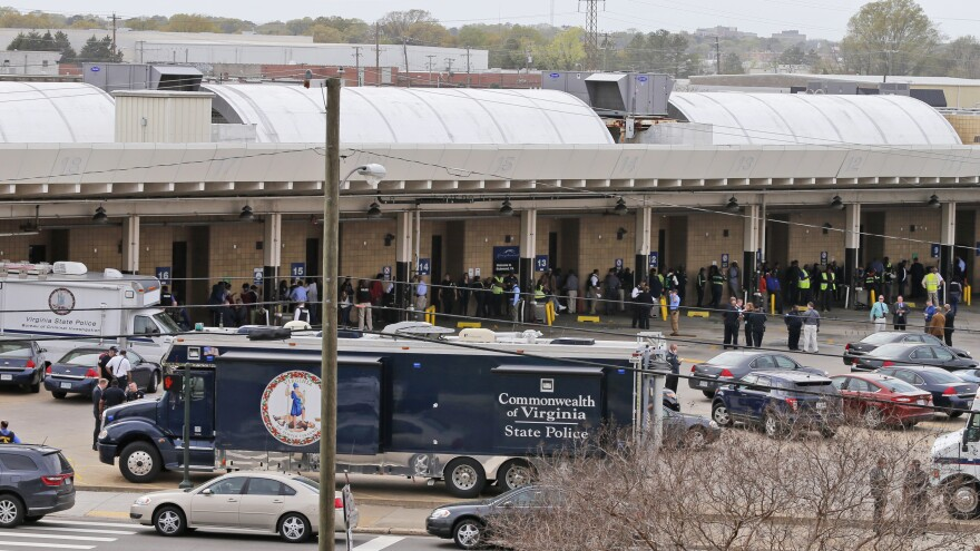 Police and rescue officials mingle with bus patrons outside the Greyhound Bus Station on Thursday in Richmond.