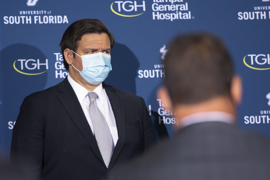 Governor Ron DeSantis stands wearing a mask, looking to the right.