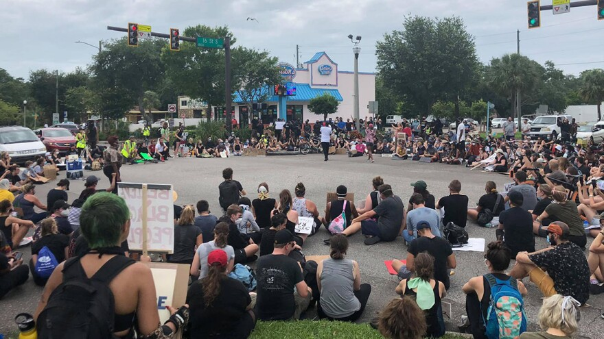 Black Lives Matter protesters sit in a large circle, blocking a busy intersection in St. Petersburg.