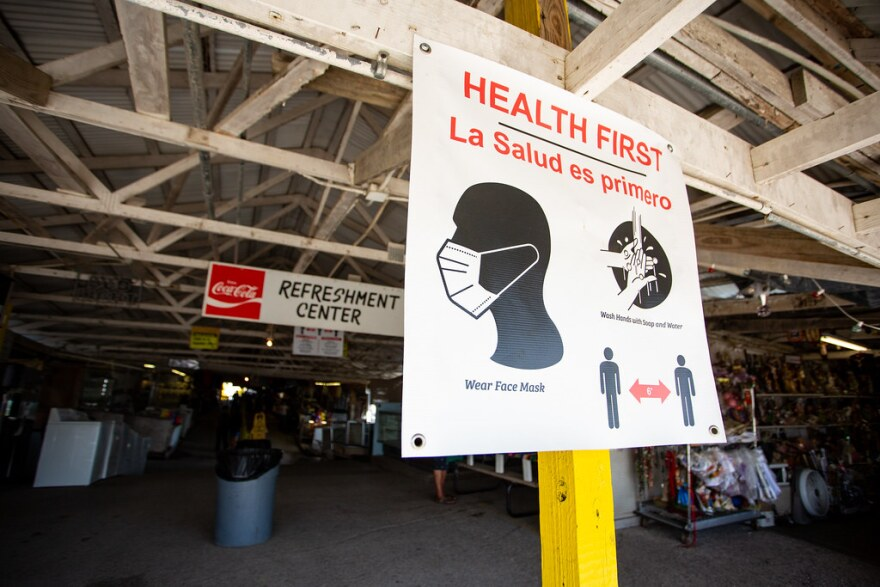 A sign at the Austin County Flea Market tells people to wear masks, social distance and wash their hands.