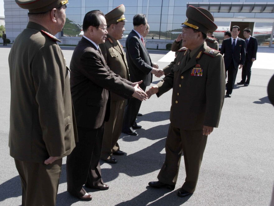 North Korea's Vice Marshal Choe Ryong Hae (front right) shakes hands with officials as he departs for China.
