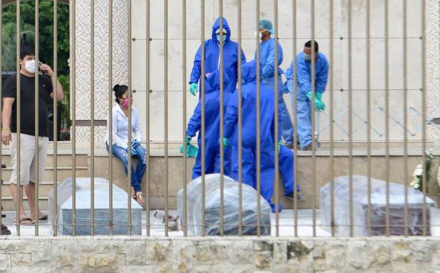 Cemetery workers in Guayaquil, Ecuador, moving corpses of COVID-19 patients from a sidelwalk last week.