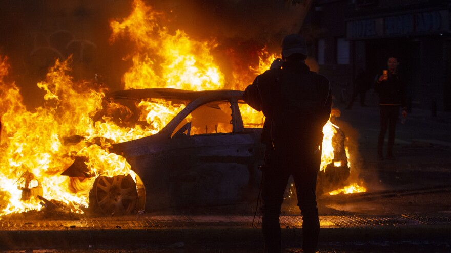 Men take pictures of a burning car during violent protests in Santiago Saturday.