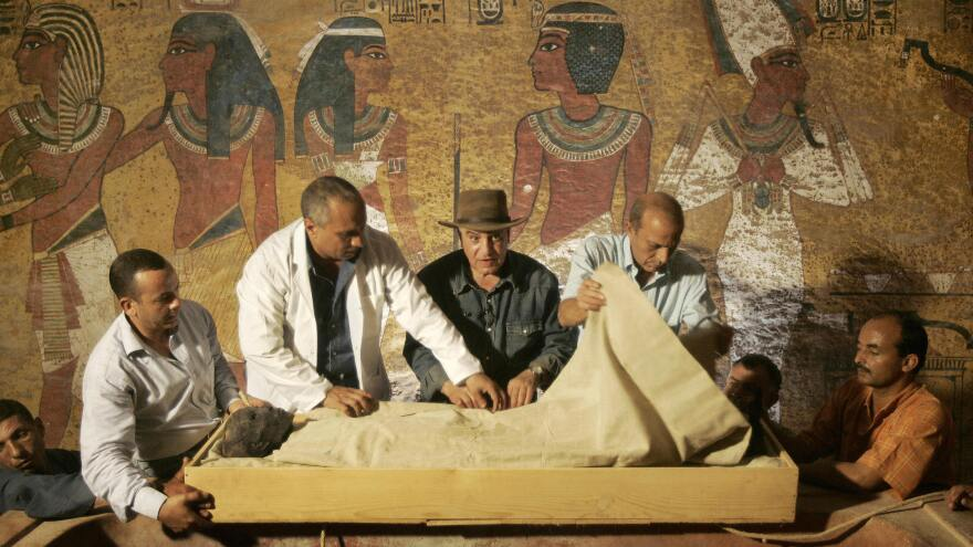 Officials remove the linen-wrapped mummy of King Tutankhamen from his stone sarcophagus in his underground tomb in the famed Valley of the Kings in Luxor in 2007. New radar scans show that other rooms may be hidden behind the tomb's walls.