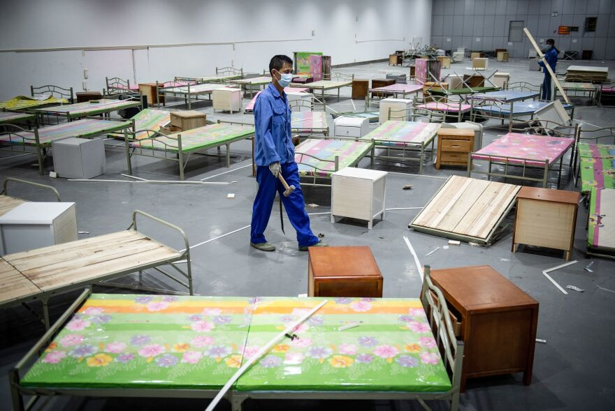 A worker walks past bed frames as workers demolish installations at Wuhan's first makeshift hospital built to treat patients infected with COVID-19 in China's central Hubei province in August.
