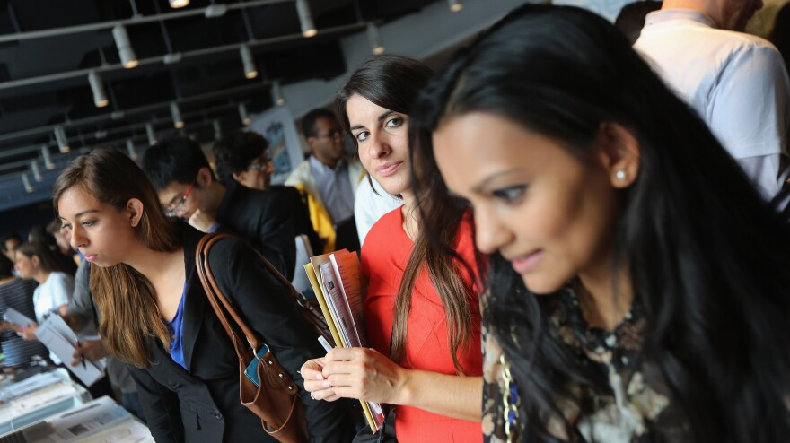 Job applicants meet potential employers at the NYC Startup Job Fair in September. Last month, the private sector created jobs while the public sector resumed laying off workers.