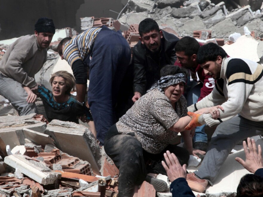 <p>People rescue two women who were trapped under debris after a powerful 7.2-magnitude earthquake in Van, eastern Turkey, on Sunday.</p>