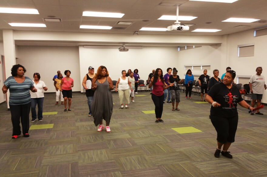 """Dawn, """"the Dancin' Deeva,"""" helps a group of women learn new moves during an adult line dancing class.  The Harvey Library offers the free class weekly."""
