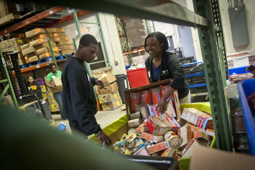 TD Bank volunteers sort donated food into barrels at the Manna Food Center in Gaithersburg in Montgomery County, Md. Poverty in the county just outside Washington, D.C., has grown by two-thirds since 2007.