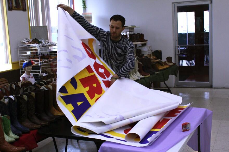 Artist Alberto Aguilar unrolls signs at El Torito grocey