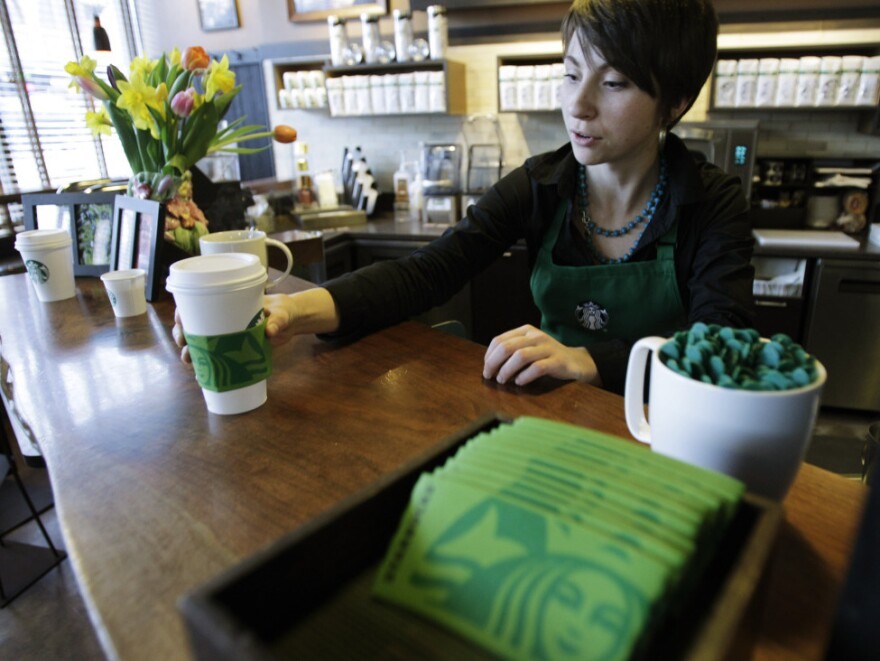 Barista Nicole Adams serves up a drink in March at a Starbucks in downtown Seattle. The company is expanding its coffee options to include a light roast and plans to create a new health and wellness brand.