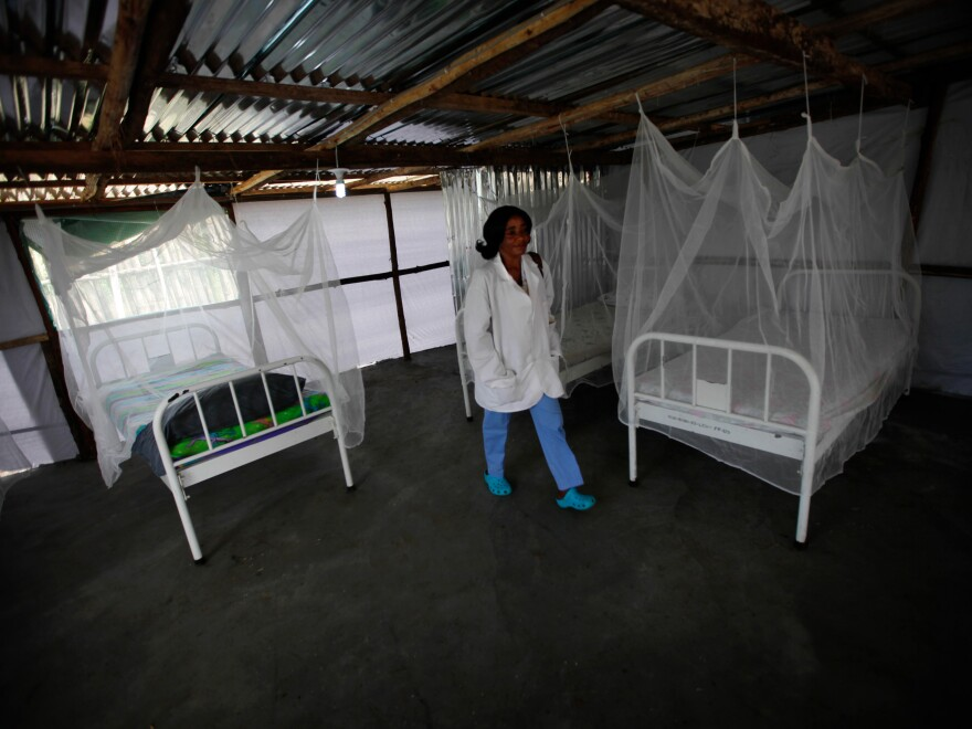 A nurse walks through a newly completed Ebola treatment unit near the Tubmanburg hospital in Liberia. It has three separate areas for suspected, probable and confirmed cases of Ebola.