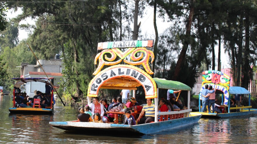 A <em>trajinera</em> called Rosalinda carries a family along the Xochimilco canals in Mexico city. The borough and its canals are a UNESCO World Heritage Site.